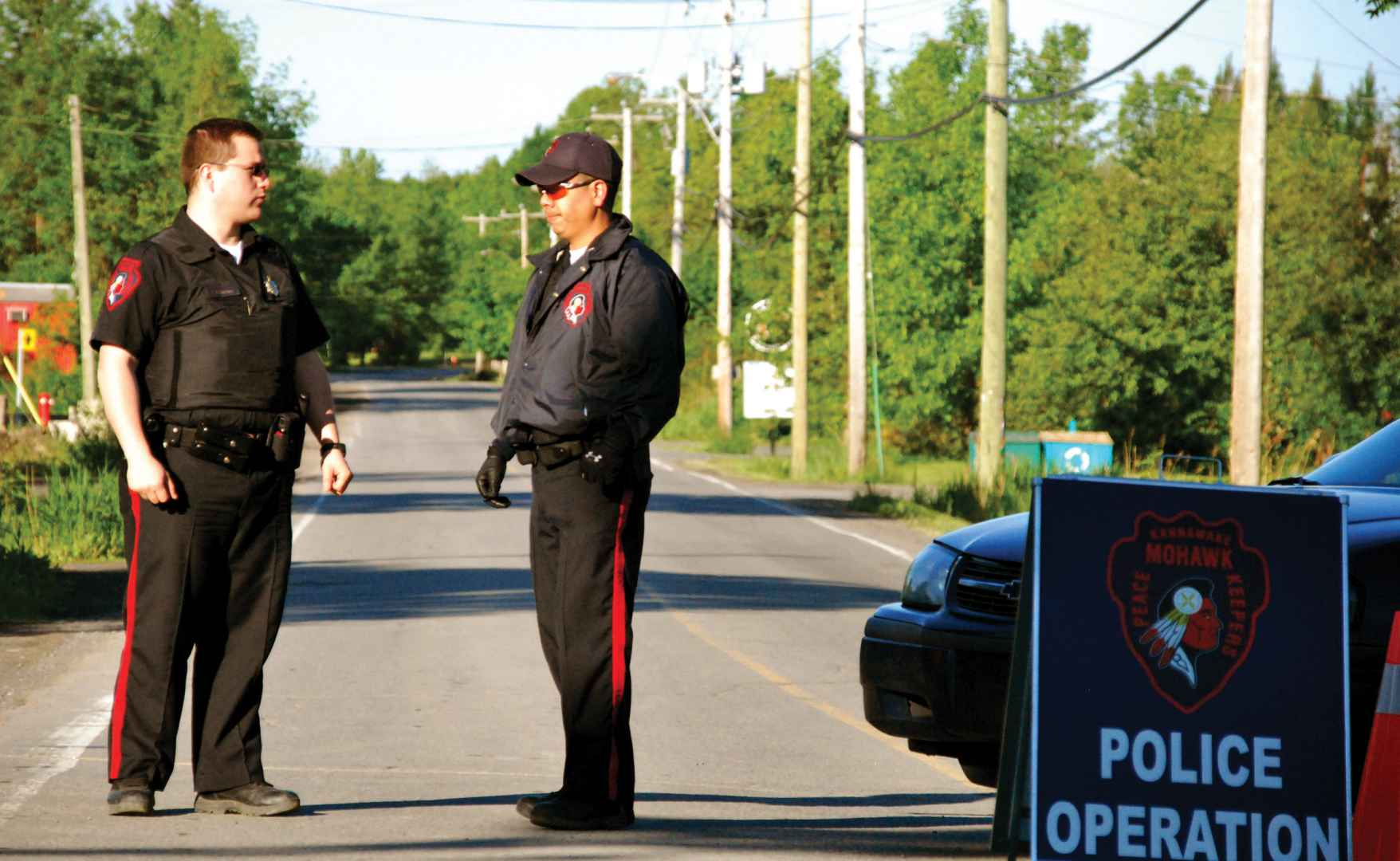 Peacekeepers Kyle Zachary and Forrest Horn stop traffic at Barnes Road the morning of the province-wide Operation Machine raid. (Steve Bonspiel, The Eastern Door)