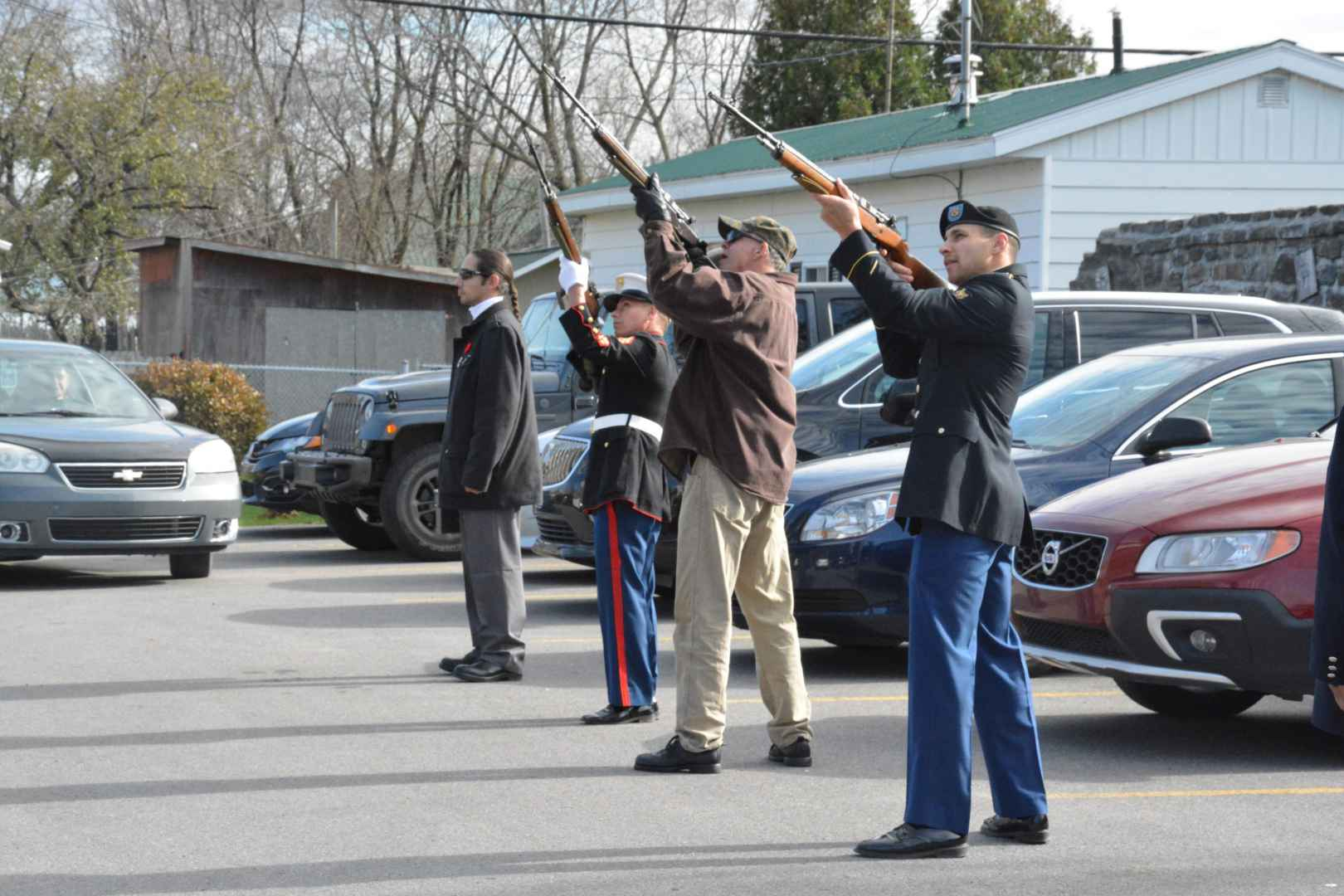 The flags were lowered to half-staff in respect of all fallen soldiers, then raised again. Community members held their ears as the Branch 219 rifle squad conducted a rifle salute. (Jessica Deer, The Eastern Door)