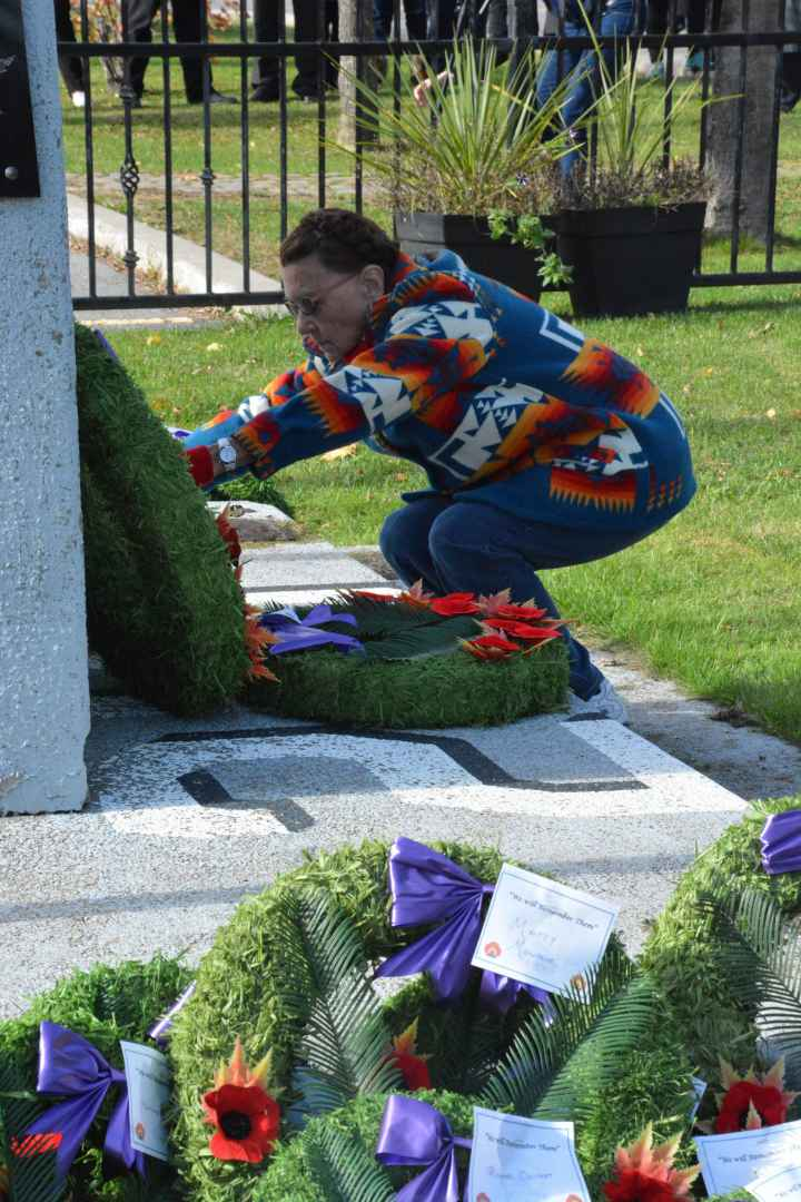 Bernice Montour adds her wreath to the dozens adorning the cenotaph at the heart of Kahnawake. (Jessica Deer, The Eastern Door)